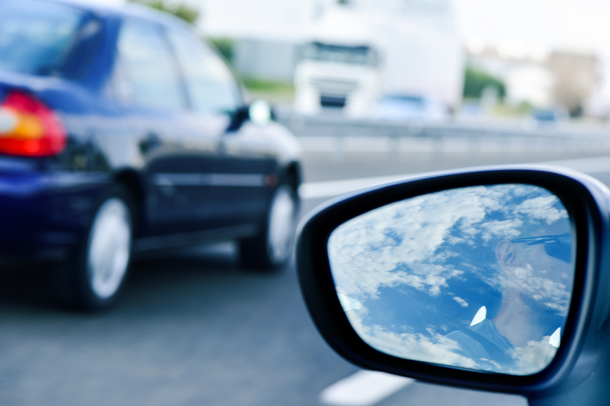 young man driving a car reflected in the wing mirror