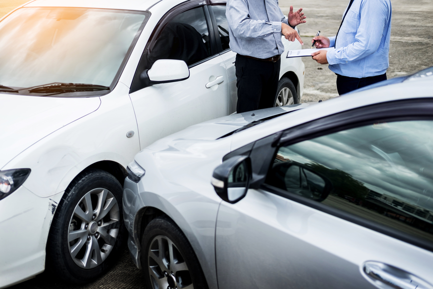 Insurance agent writing on clipboard while examining car after a
